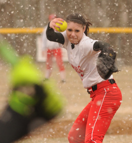 FIRST PLACE, SPORTS PHOTOGRAPHY: Saranac pitcher Nikki Donah winds up before delivering the ball to Saranac Lake batter Briana Fenton during the third inning of the Champlain Valley Athletic Conference home opener for Saranac Lake April 12, 2016. Heavy snow fell on the diamond during the middle stages of the game before giving way to bright sunshine. (Enterprise photo — Lou Reuter)
