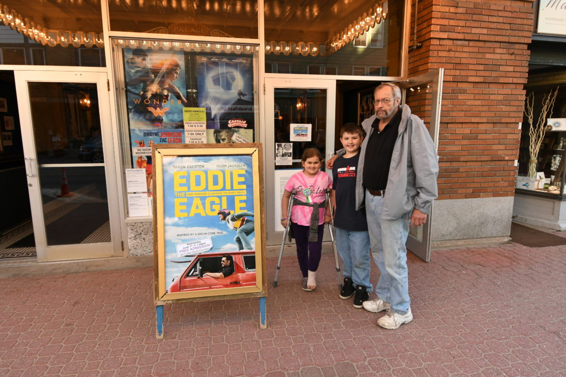 "From the right, Lake Placid's Alan, Emma and Ayden Patterson stand in front of the Palace Theater Wednesday evening before watching ""Eddie the Eagle,"" the first movie show in this year's Lake Placid Film Forum. (Enterprise photo — Lou Reuter)"