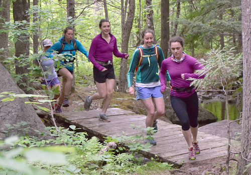 Sophie McClelland leads Kate Barton and Janey McClelland over a bridge on the 11.5-mile course during last year's Great Adirondack Trail Run.  (Enterprise file photo — Justin A. Levine)