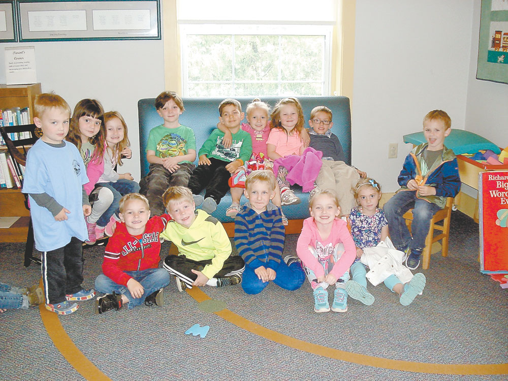 Children who attended Story Time on May 25  are shown sitting on a new sofa in the Elinor B. Preis Children's Room. The sofa was purchased with memorial funds donated in memory of Helen Sprague who worked as library assistant at the Saranac Lake Free Library for 44 years. Among her many duties, Helen was in charge of the Story Time Program, arranging for the reader each week and organizing the Holiday Parties. She retired in 2011. (Photo provided — Pat Wiley)