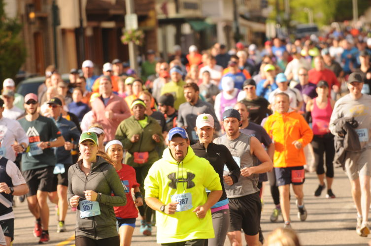 Runners make their way up Main Street during the 2016 Lake Placid Marathon and Half. (Enterprise photo — Lou Reuter)