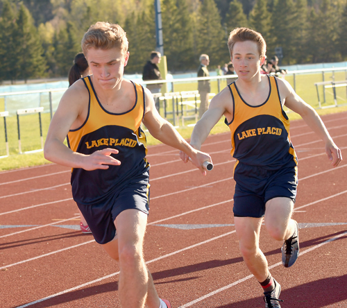 Lake Placid senior Stuart Baird takes the baton from teammate Henry McGrew during a home track meet on May 11. Baird will compete today in the 4x800 relay at the NYSPHSAA track and field championships and then attempt his first marathon in Lake Placid on Sunday. (Enterprise photo — Lou Reuter)