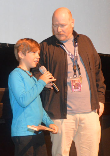 "Trey Frantz, 9, of Lake Placid, accepts the Best Actor award during Friday night's screenings of the three films college students created as part of the ""Sleepless in Lake Placid"" film competition as part of the Lake Placid Film Forum. (Enterprise photo — Antonio Olivero)"