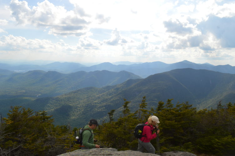 Hikers complete a through-hike of the Dix range by crossing the 4,839-foot summit of Dix Mountain before heading down to the junction with the Hunters Pass trail. The High Peaks Wilderness is in view at rear. (Enterprise photo — Antonio Olivero)