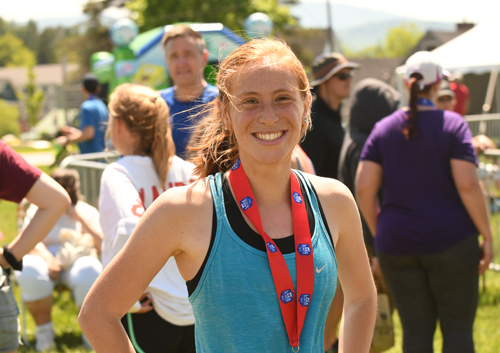 Maddie Dery smiles with her medal after winning the women's marathon in Sunday's Lake Placid Marathon. Prior to Sunday, the longest distance Dery ever ran was just over 15 miles. (Enterprise photo — Lou Reuter)
