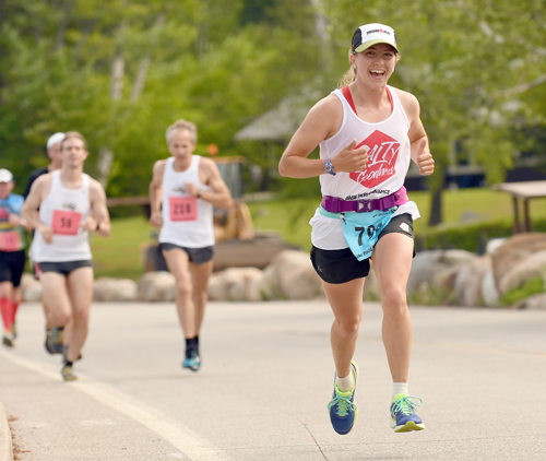 Lake Placid's Elizabeth Izzo smiles while running in Sunday's 13th annual Lake Placid Marathon. The 25-year-old was the runner-up in the women's half-marathon field. (Enterprise photo — Lou Reuter)