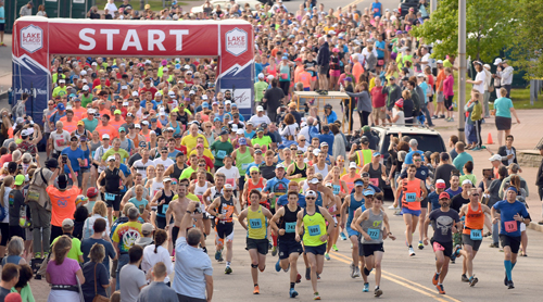 A field of nearly 1,000 runners bathe Main Street in an array of colors as they leave the starting line Sunday morning during the 13th annual Lake Placid Marathon. (Enterprise photo — Lou Reuter)