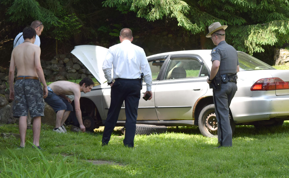 Neighbor Joe Boyle, bending over, shows state police where Gary Yarrish was pulled out from under a Honda Accord that fell on him Monday on Cantwell Way in Saranac Lake. Yarrish's son Dustin stands at left. (Enterprise photo — Chris Knight)