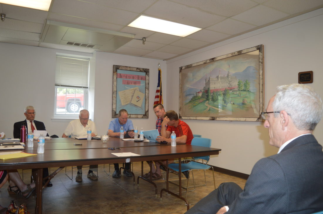 Adirondack Historical Association Executive Director David Kahn, foreground, listens as Lake Placid Mayor Craig Randall, far left, reads aloud from the village Board of Trustees' determination and findings to enter into an official eminent domain proceeding to acquire the museum's Main Street properties to construct a public parking garage. (Enterprise photo — Antonio Olivero)