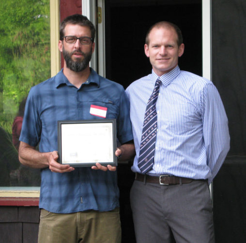 Jason Smith, left, of Adirondack Lakes and Trails Outfitters and Dewey Mountain Recreation Center, stands with Saranac Lake Area Chamber of Commerce Executive Director Johnny Muldowney after Smith was named Citizen of the Year at the chamber's dinner Tuesday at the Porcupine Inn. (Enterprise photo — Susan  Moore)