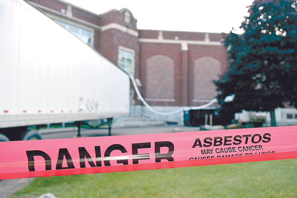 Red caution tape is strung around the half-circle at Petrova Elementary/Saranac Lake Middle School in Saranac Lake where crews from Two Brothers Contracting are removing vermiculite, which can contain asbestos, found in the building's third-floor ceiling. (Enterprise photo — Chris Knight)