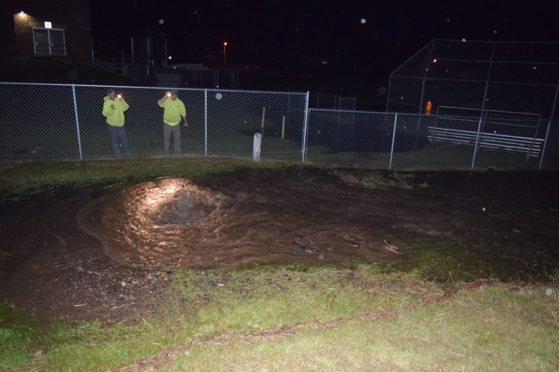 Village of Saranac Lake workers check a water main break near the Saranac Lake Middle School gym Thursday night. (Enterprise photo — Chris Knight)