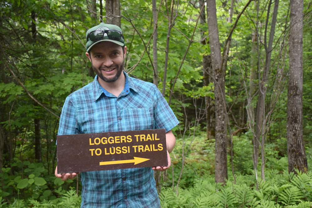 Josh Wilson, executive director of Barkeater Trails Alliance, shows off a new state sign near the Lussi Trails outside of Lake Placid. (Enterprise photo — Justin A. Levine)