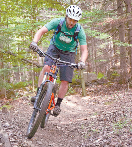 Josh Wilson, executive director of Barkeater Trails Alliance (BETA), rides a mountain bike at Dewey Mountain Recreation Area in Saranac Lake in July 2016. Dewey and the Mount Pisgah Ski Center added mountain bike trails in recent years in the Saranac Lake area, and now the state, with BETA's help, plans to add more in the Saranac Lakes Wild Forest. (Enterprise photo — Justin A. Levine)
