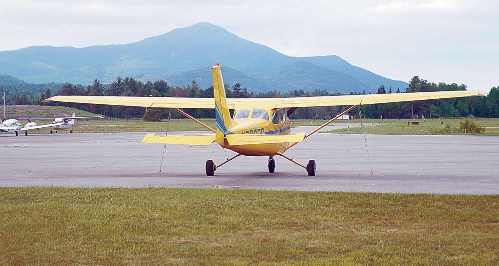 Whiteface Mountain can be seen to the north from the Lake Placid Airport, where planes are parked Friday evening. (Enterprise photo — Antonio Olivero)
