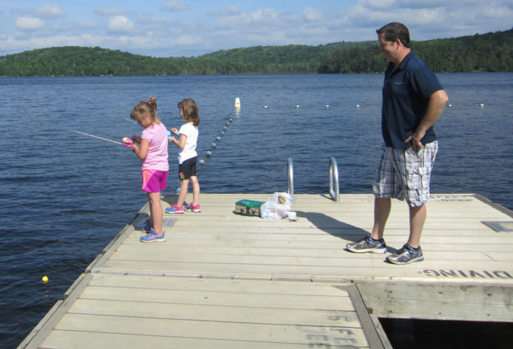 Jason Colby watches his daughters Addy, 7, and Emii, 5, fish during the Saranac Lake Fish and Game Club's Father's Day Fishing Derby on Lake Colby.  (Photo provided — Diane Chase)