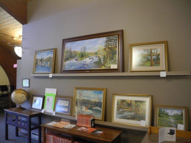 A selection of paintings by Helen Macro hangs in the Goff-Nelson Memorial Library in Tupper Lake.  (Enterprise photo — Ben Gocker)