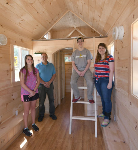 Saranac Lake High School seniors Andrea Boon, left, Josh Howland, third from left, and Brooke Smith, right, join instructor Clarence Brockway inside a tiny home their class built. (Enterprise photo — Lou Reuter)