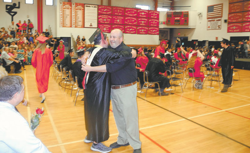 Senior class President Logan Savage, who delivered the evening's salutatorian address, hugs his father Chris Savage at the close of Tupper Lake High School's commencement ceremony Friday. (Enterprise photo — Ben Gocker)