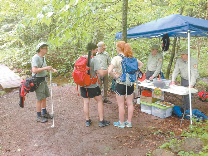 Adirondack 46ers trailhead stewards Ron Konowitz, center, Joe Ryan and Brian Hoody, talk with some hikers at the Cascade Mountain trailhead outside of Lake Placid Saturday morning. The trio of stewards saw nearly 500 hikers pass by their tent during an eight-hour shift. (Enterprise photo — Justin A. Levine)