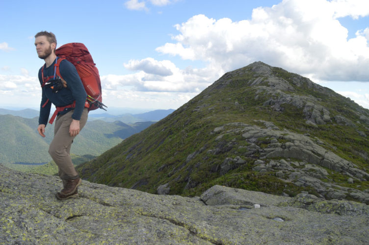 Hugo Lafontaine of Montreal traverses Little Haystack Mountain, the 4,960-foot summit of Haystack Mountain, the state's third highest point, in view behind him Saturday afternoon. (Enterprise photo — Antonio Olivero)
