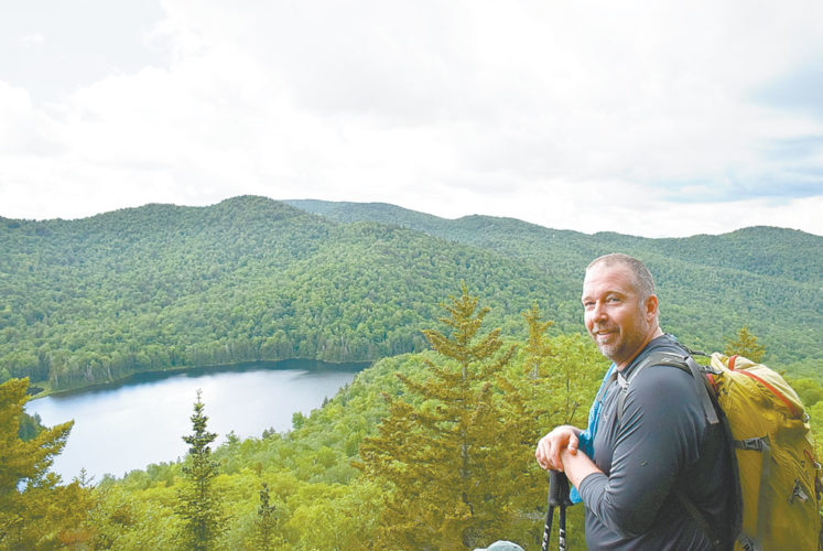 Spencer Morrisey, a Cranberry Lake resident, smiles at the top of his 1,000th named Adirondack peak. Morrisey led a group of hikers up Peaked Mountain near North Creek on Sunday. (Enterprise photo — Justin A. Levine)