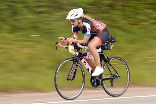 Lake Placid's Elizabeth Izzo pedals her bike Saturday in the Tinman. She finished second in her age group and sixth overall in the women's field. (Enterprise photo — Lou Reuter)