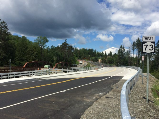 """This past weekend those traveling to and from Lake Placid on state Route 73 for the first time traversed the new """"Ski Jumps bridge"""" over the AuSable River just past River Road. Lake Placid Mayor Craig Randall said to his knowledge the bridge was opened to car and bicycle traffic Friday after more than a year of construction work by the state Department of Transportation. Randall added that he has no current information on when construction crews will permanently finish in the area or when the old bridge will be removed. """"It's a wonderful, wonderful improvement to come around that curve and not worry about oncoming traffic,"""" the mayor said. """"And it's much safer for a cyclist going over that bridge now."""" (Enterprise photo – Don Hare)"""