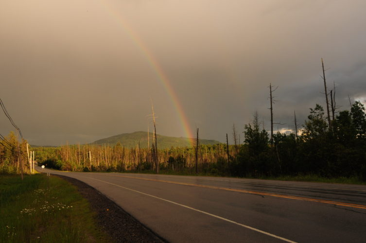 A rainbow appears to rise out of the forest in front of Scarface Mountain in this picture taken along state Route 86 Monday evening between Saranac Lake and Ray Brook. (Enterprise photo — Lou Reuter)