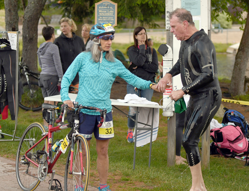 Nancie Battaglia of Lake Placid is ready to pedal after receiving a tag from Saranac Lake's Karl Zaunbrecher during Monday's High Peaks Cyclery mini triathlon. The pair teamed up for the race, with Zaunbrecher taking on the 400-yard swim leg and Battaglia rounding out the race with the bike and run portions. (Enterprise photo — Lou Reuter)