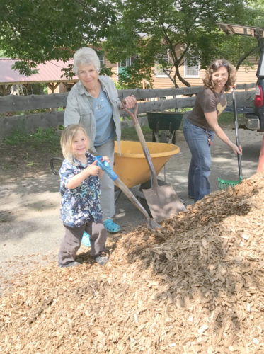 Three generations shovel mulch for the play area at Northern Lights School in Saranac Lake this week, including, from left, Sebastian, Dots and Julia Goran. (Enterprise photo — Catherine Moore)