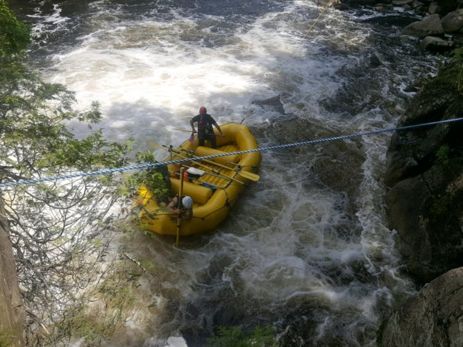 Rescue personnel use a Zodiac inflatable fire rescue boat and cameras attached to the end of poles in the raging whitewater of the AuSable River near the popular Wilmington Flume swimming hole Tuesday afternoon in an attempt to find the body of a 31-year-old man from Ithaca who they say drowned at the location Monday afternoon when swimming with fellow friends who were camping in the area. (Photo provided — Essex County Coroner's Office)