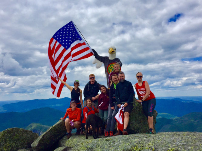 New Adirondack 46er Rob Van Avery dons an eagle suit and waves an American flag atop the 4,840-foot summit of Iroquois Peak, the eighth highest mountain in the Adirondacks, on Tuesday, joined by a group of friends and fellow hikers. Van Avery  finished his summiting of the 46 highest peaks in the Adirondacks by scaling the mountain on July 4. (Photo provided)