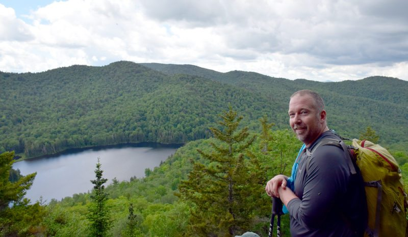 Spencer Morrissey smiles at the summit of Peaked Mountain while overlooking Peaked Mountain Pond on June 24. It was the 1,000th named peak in the Adirondacks that he had climbed. (Enterprise photo — Justin A. Levine)