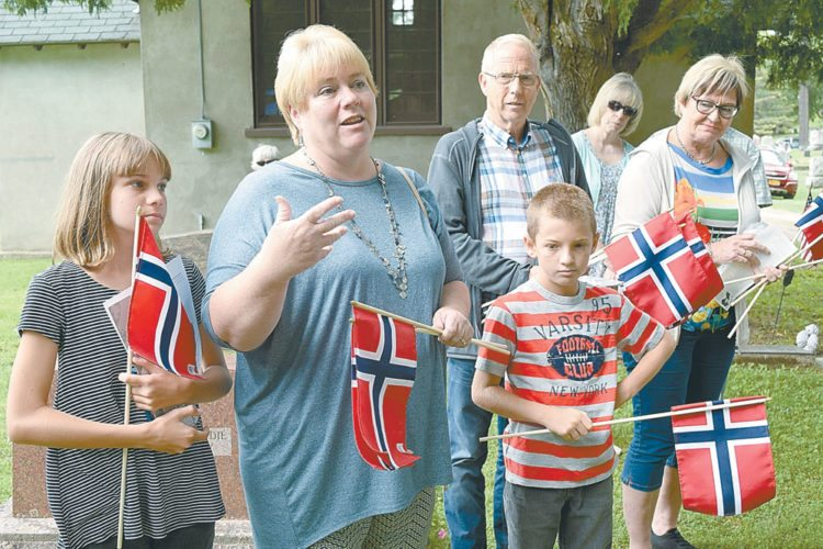 Kari Harrington talks about her father, the late Knute Grytebust, a Norwegian sailor who came to Saranac Lake to cure from tuberculosis during World War II, Monday in Pine Ridge Cemetery. Standing behind her is her cousin Leif Sperre, who lives in Norway. (Enterprise photo — Chris Knight)