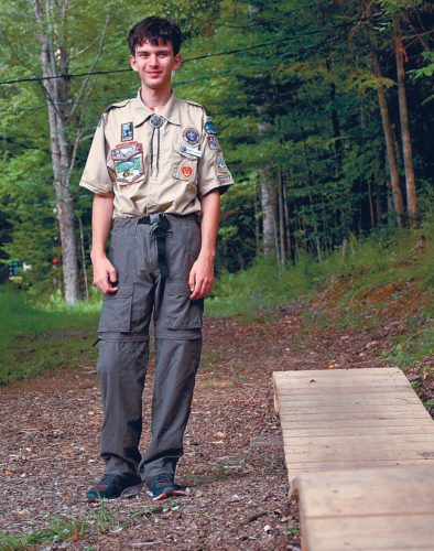 Bennett Martino of Onchiota stands next to one of the mountain biking bridges he built for Dewey Mountain in Saranac Lake last year. Martino, who completed the construction as part of his Eagle Scout project, built more than 200 feet of bridges so that mountain bikers have more obstacles to ride on. He was awarded with the Eagle Scout designation at a ceremony at the Dewey Mountain Lodge in June. (Enterprise photo — Justin A. Levine)