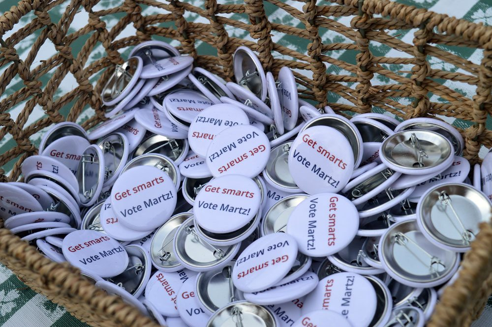 Campaign pins rest in a basket for attendees to take during Democrat Emily Martz's congressional campaign announcement at the Wednesday evening at Riverside Park in Saranac Lake. (Enterprise photo — Antonio Olivero)