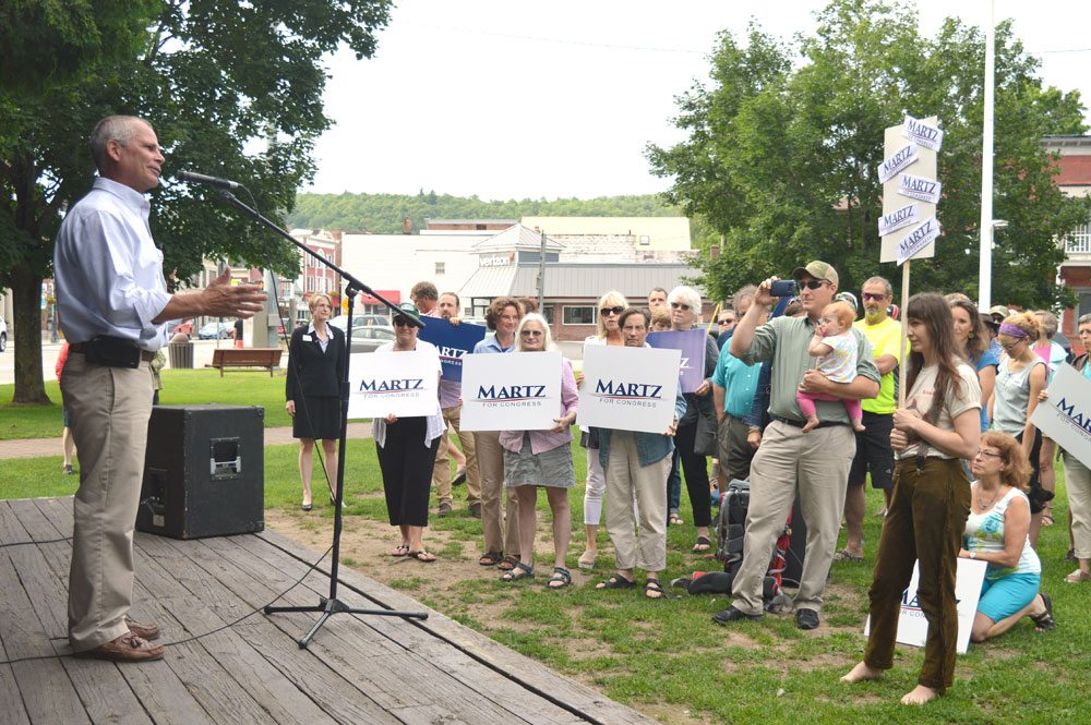 Saranac Lake Mayor Clyde Rabideau speaks before Democrat Emily Martz of Saranac Lake formally announces her congressional campaign Wednesday evening in Riverside Park in Saranac Lake, while Martz supporters hold up campaign signs in the crowd. (Enterprise photo — Antonio Olivero)