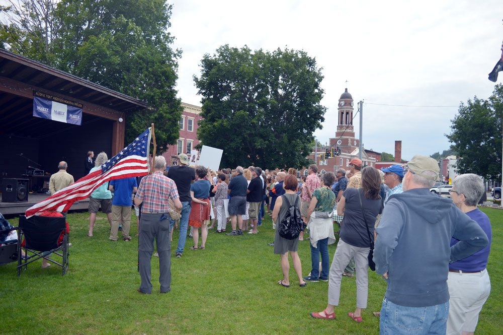 Dozens of people listen as Democrat Emily Martz of Saranac Lake formally announces her congressional candidacy at the bandshell Wednesday evening at Riverside Park in Saranac Lake, with the Harrietstown Town Hall clock tower in the background. (Enterprise photo — Antonio Olivero)