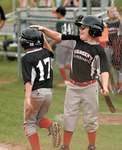 Mason Fowler, right, greets Shaheen's IGA Market teammate Knaullyn Durfee, who is returning to the bench after beating a tag at home plate during Wednesday's Minor League game against Sandy Hayes Reality played at the Bloomingdale Volunteer Fire Department. Shaheen's won the contest 12-4. (Enterprise photo — Lou Reuter)