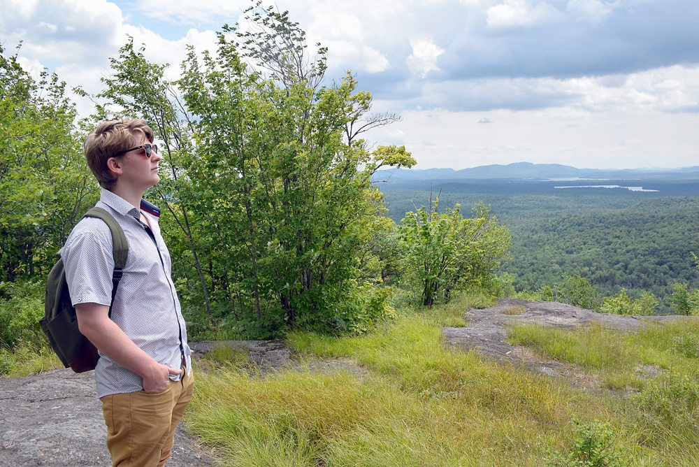 Kevin Shea takes in the view from the south summit of Floodwood Mountain on Monday, July 10. The second summit can be reached following a herd path and offers views of Iron Mountain, Tupper Lake and Rollins Pond. (Enterprise photo — Justin A. Levine)