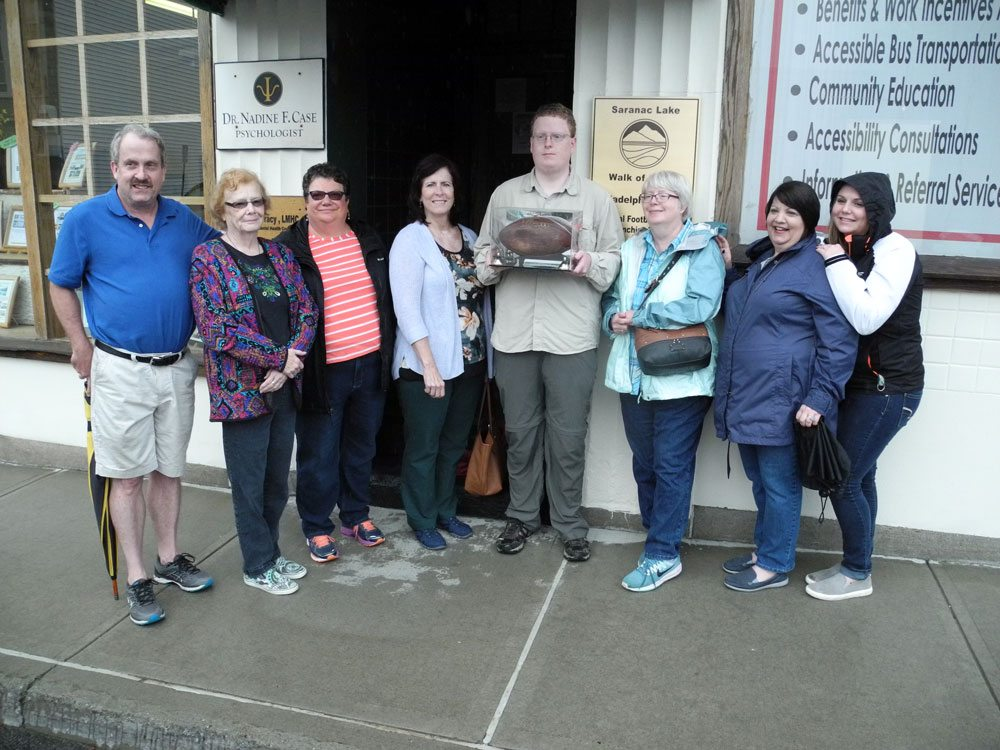 Descendents of Caroline Stott, who cooked for the Philadelphia Eagles football players as they trained in Saranac Lake in the 1940s, pose Thursday with a signed football they gave her in 1947. They are standing in front of a new Saranac Lake Walk of Fame plaque for the team on the Grant Building. (Enterprise photo — Aaron Cerbone)
