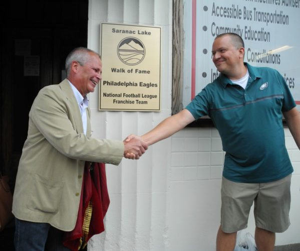 Philadelphia  Eagles officer Jon Ferrari, right, and  Saranac Lake Mayor Clyde Rabideau shake hands after unveiling a Saranac Lake Walk of Fame plaque for the team, which once trained in the village. (Enterprise photo — Aaron Cerbone)