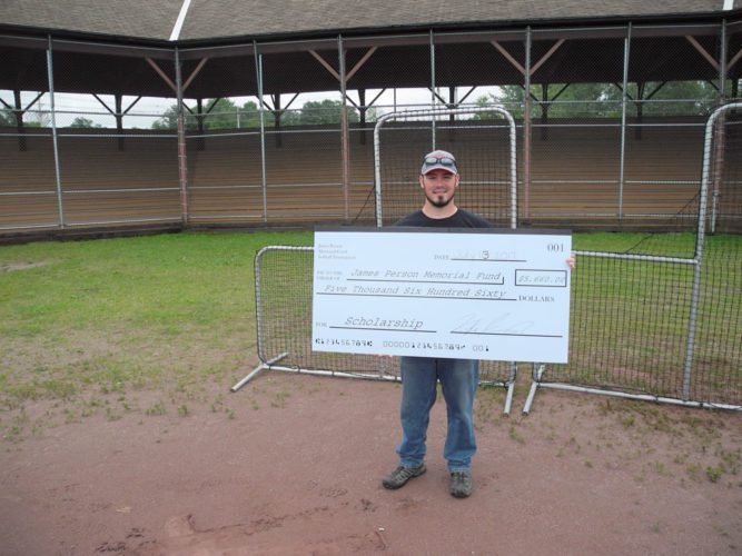 Kyle Kavanagh, who organizes the annual James Person Memorial Coed Softball Tournament, holds a $5,660 check, given to scholarship winners, at the ballfield at the Tupper Lake Municipal Park. (Enterprise photo — Aaron Cerbone)
