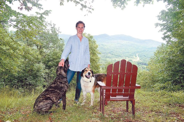Katie Wilson smiles Friday with her neighbor's dog Lucy, left, and her dog Derby after hiking a private trail to a lookout in her hometown of Keene. (Enterprise photo — Antonio Olivero)