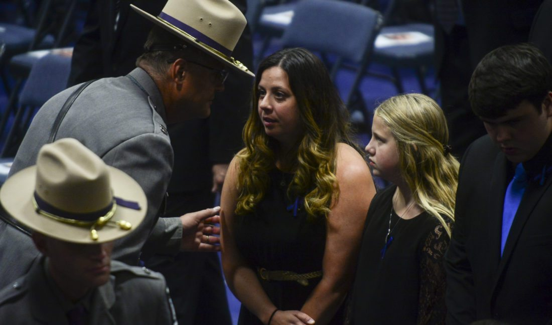 A New York state trooper walks Suzanne Davis and her children to their seats as family and friends come together to say goodbye to fallen trooper Joel Davis during a funeral service on Saturday at Fort Drum. (Photo provided — Daytona Niles, Watertown Daily Times)