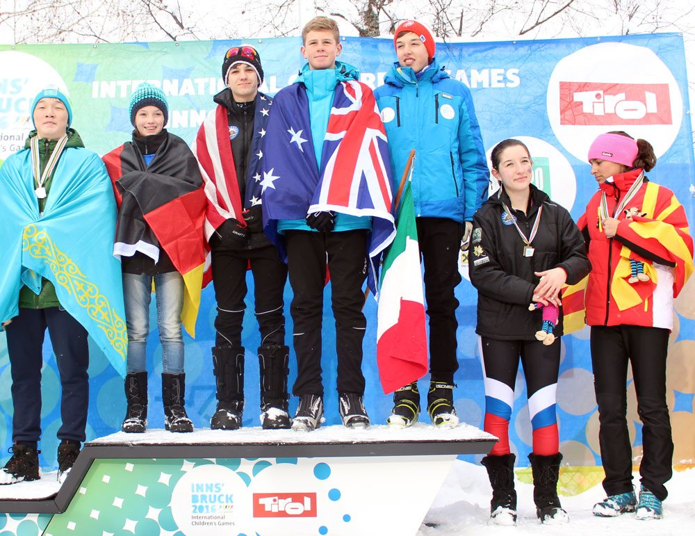 Lake Placid's Jesse Izzo, third from left, and Anya Morgan, second from right, stand on a podium after a nordic skiing race at the International Children's Games in January 2016 in Innsbruck, Austria. (Photo provided)