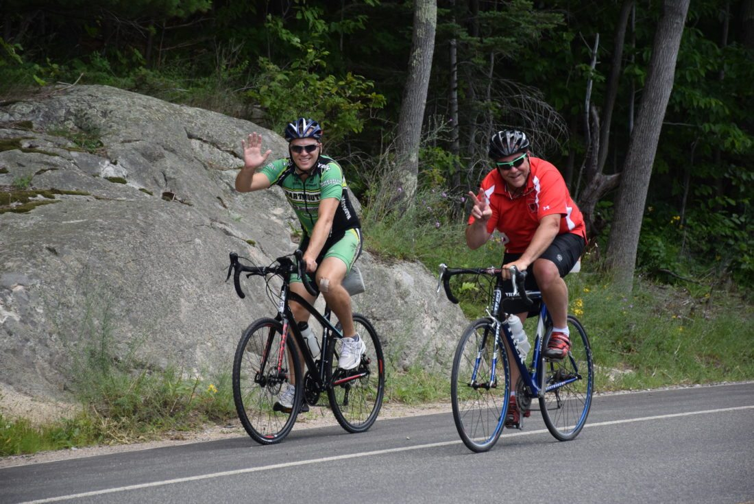 Mike Jablonski, left, and Dave Swits wave as they near the end of their 30-mile bike ride around Wilmington and Jay on Sunday as part of the Ride for the River, a benefit for the Ausable River Association. (Enterprise photo — Justin A. Levine)
