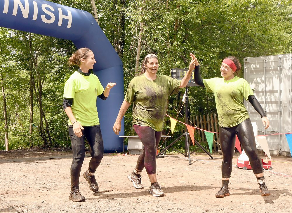 From the left, Northeast Taekwondo team members Melody Blackmore, Amanda Lavigne and Danielle Brown are all smiles after reaching the finish line in Saturday's Warrior Run in Tupper Lake. (Enterprise photo — Lou Reuter)