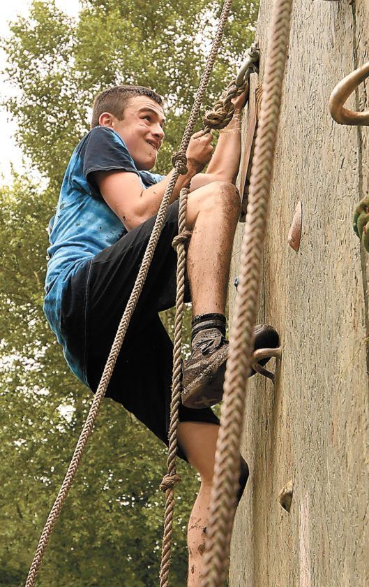"""Shawn Allen scales the climbing wall during Saturday's Warrior Run in Tupper Lake. He joined three friends as members of the Turtle Running Team that competed with the motto """"We're slow as shell."""" (Enterprise photo — Lou Reuter)"""